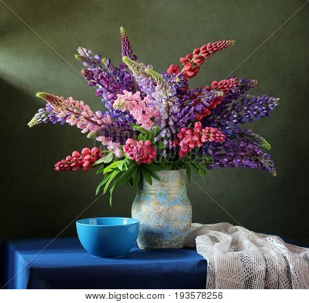 Bouquet of flowers in a vase. Still life with pink and purple lupins.