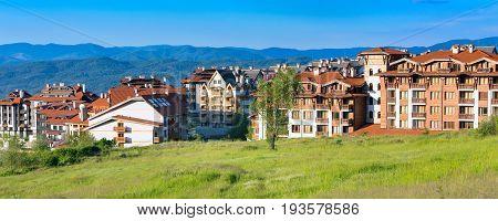 Bansko, Bulgaria - June 13, 2017: Wooden chalet hotel houses and summer mountains panoramic banner in bulgarian all season resort