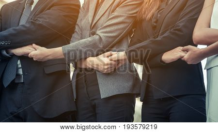 Business people holding hands together showing teamwork people unity corporate for businesses success.