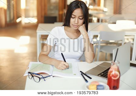 Young schoolgirl getting ready for her classes in an open space library or cafe drinking lemonade using laptop writing in her coursebook.