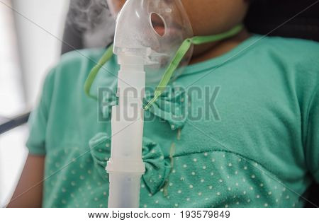 Young woman doing inhalation nebulizer with smoke from oxygen mask in the hospital.