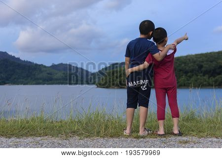 Love of brother and brother hugging and happy with looking view of mountain and lake.