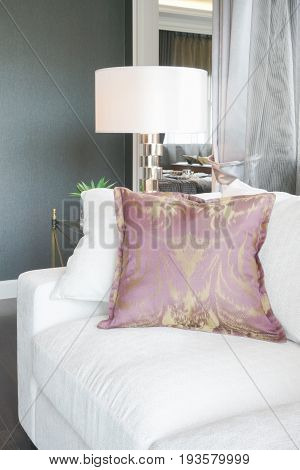White Sofa With Purple Pillow, Reading Lamp In Background