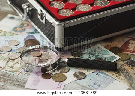 Different Old Collector's Coins And Banknotes With A Magnifying Glass