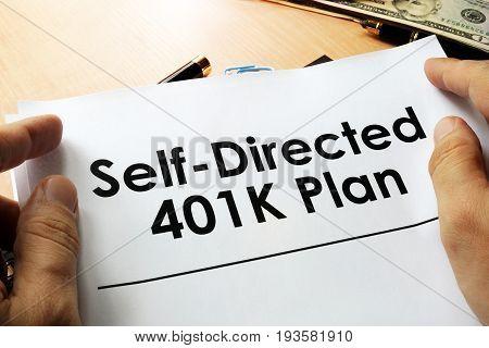 Self directed 401k plan written on a paper.
