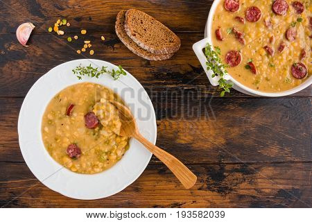 Hearty and healthy split pea and smoked sausage soup with green thyme in a white plate and casserole on the wooden table top view.