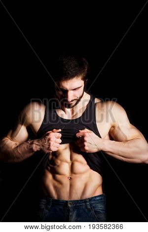 Perfect man shows his six pack abs. Muscular and sexy torso of young male. Hunk with athletic body holding shirt, striptease