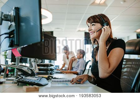 Casual businesswoman working at desk using computer and headset in the office. Focus on woman sitting in foreground with colleagues working in background.