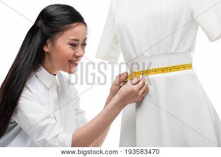 Happy Young Asian Dressmaker Measuring Stylish White Dress On Dummy, Isolated On White