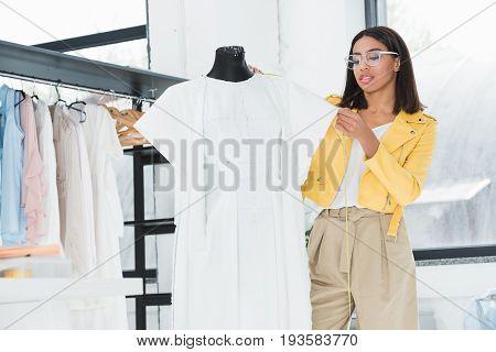 Stylish Young Fashion Designer Examining White Dress On Dummy