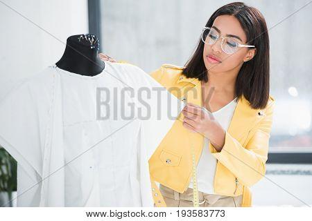Serious Young Fashion Designer Measuring White Stylish Dress On Dummy