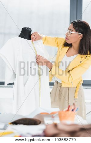Stylish Young Woman Holding Measuring Tape And Working With Dummy Indoors