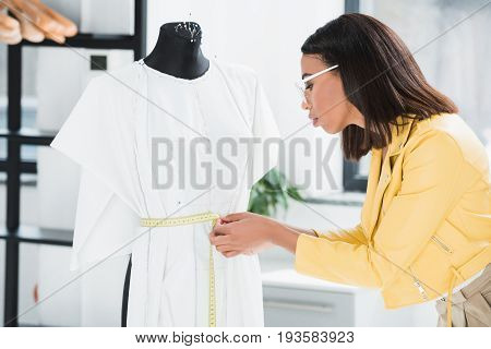 Attractive Young Seamstress In Eyeglasses Measuring Stylish Dress On Dummy