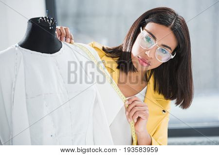 Beautiful Young Woman In Eyeglasses Measuring Dummy With Tape