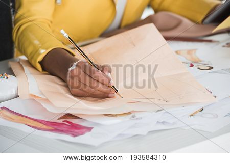 partial view of fashion designer working at table in clothing design studio