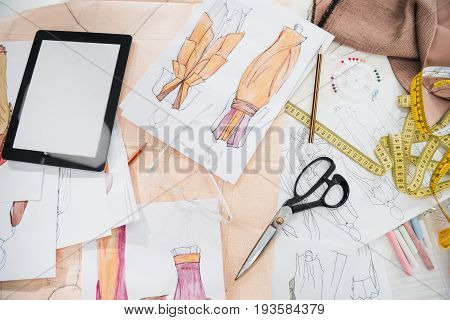 Close Up View Of Various Design Supplies, Clothing Sketches And Digital Tablet