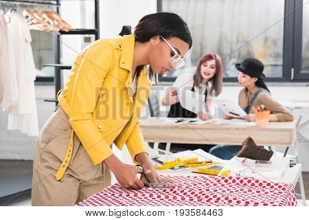Young African American Dressmaker Cutting Fabric While Her Colleagues Talking On Background