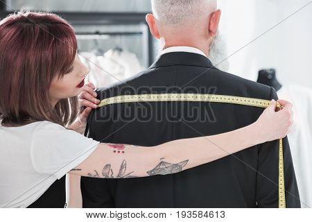 young tailor fitting grey haired man with measuring tape
