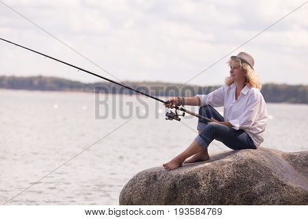 mature woman fisher sitting on sea rock