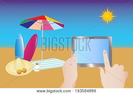 Beach umbrella towel straw hat glasses and surfboards are located on the beach. The hand touching the empty tablet screen. Empty tablet screen is ready for your text.