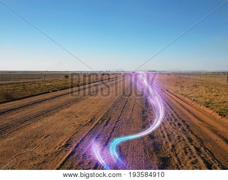 Country view of a long and straight dirt road leading into the distant horizon with light beam