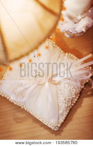 two gold wedding rings on white lace wedding pillow