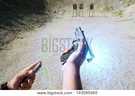 Man loading hand gun at firing range, focus on hands