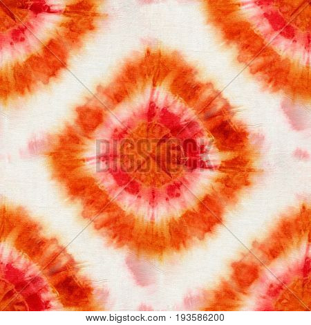 Seamless tie-dye pattern of red and orange color on white silk. Hand painting fabrics - nodular batik. Shibori dyeing.