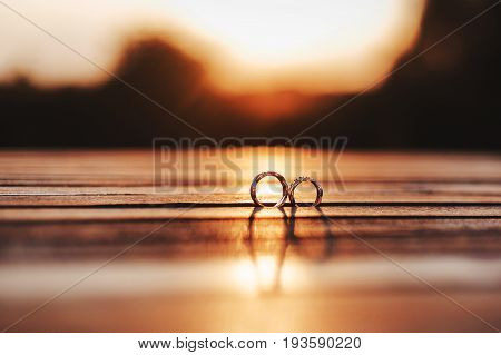 two gold wedding rings on wooden background against summer sunset