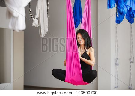 Aerial antigravity yoga girl in lotus pose on pink silk hammock, woman does aerial yoga exercises, meditates in calm position trying to achieve peaceful state of mind and body