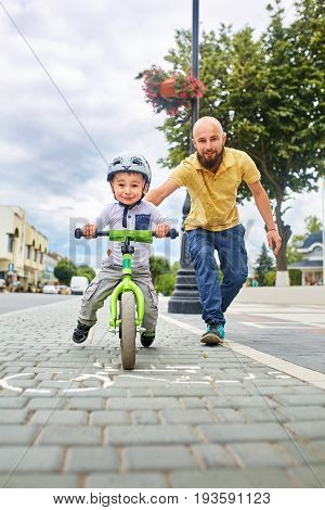 Father teaching his son to ride a bike. Happy family concept.
