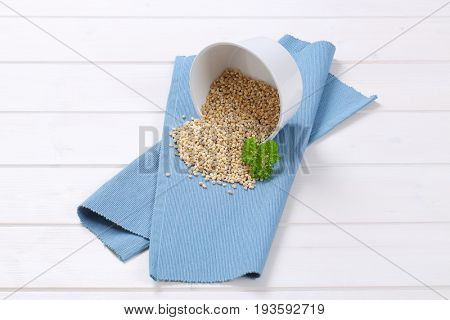 bowl of pearl barley spilt out on blue place mat