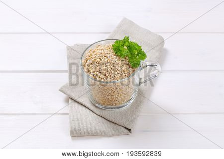 cup of pearl barley on on beige place mat