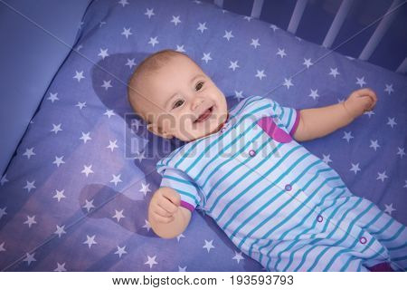 Cute little baby lying in crib at home