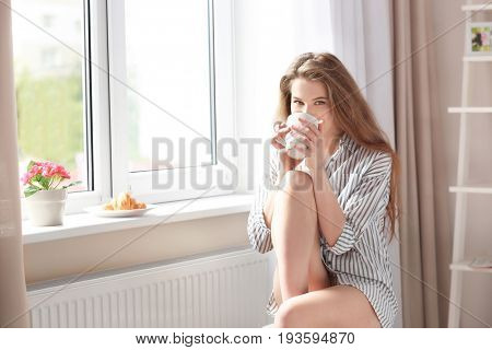 Morning of beautiful young woman having breakfast while sitting near window at home