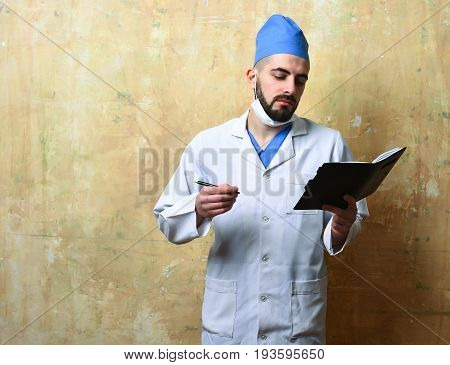 Doctor at work. Unshaved doctor in white coat and blue cap looks at notebook with serious face expression on beige background with copy space