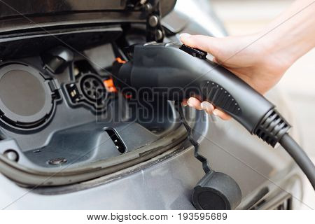 Eco-friendly vehicle. The focus being on a delicate female hand holding an electrical nozzle being about to plug it in into the inlet and charge the electric car