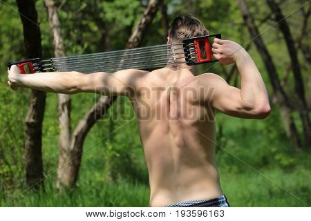 Strong Sportsman With Professional Expander Shows His Back Muscles