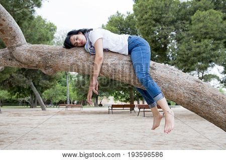 Pretty Attractive Woman Wearing Causal Clothes Sleeping In A Tree.