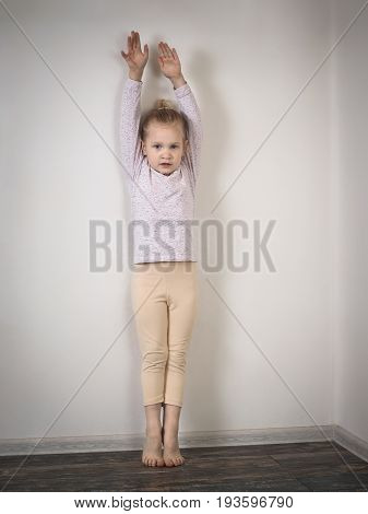Little girl standing against the wall on tiptoe with raised arms. The child wants to grow up