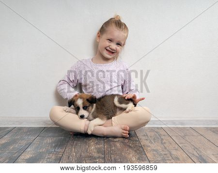 Happy girl with puppy on her lap. The child sits on the floor with the dog