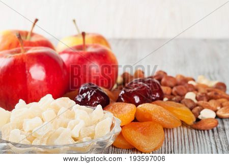 Pieces of dried pineapple apricot nuts and red apples on a wooden background