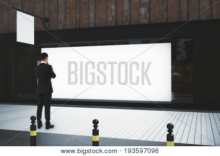 Thoughtful businessman looking at storefront with billboard and stopper. Advertisement concept. Mock up 3D Rendering