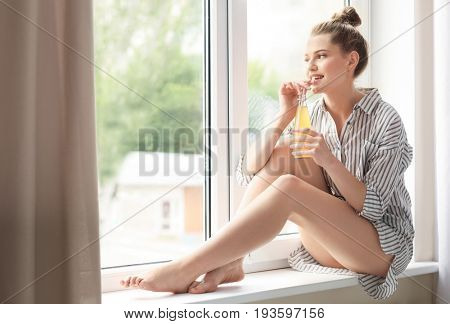 Morning of beautiful young woman drinking juice while sitting on window sill at home
