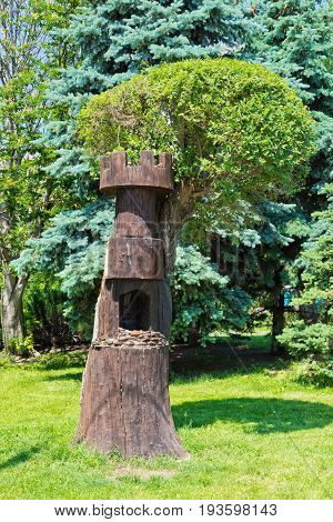 Carved from solid wood feeder for birds and small animals in the Park area in the shape of a castle tower