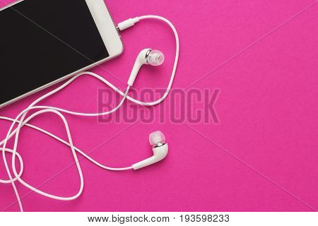 studio shot of smartphone and earbuds on bright purple background