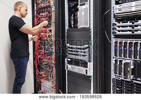Side view of mid adult male IT consultant checking with network cables connected to servers in datacenter