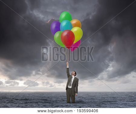 Young businessman in a suit is rescued using balloons