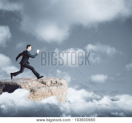 Side view of young businessman on mountain top running towards gap on dull sky background. Danger concept