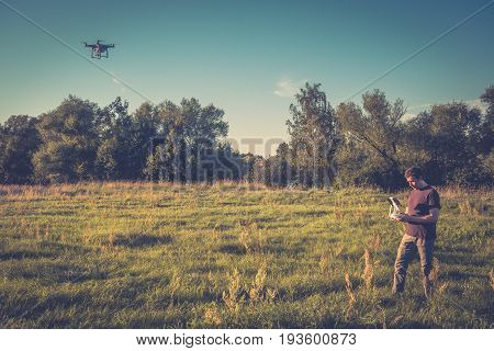 Man operating a drone quad copter with digital camera in a park